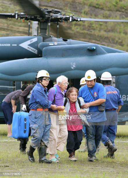 Members of Kuma village fire brigade help an elderly couple after they were evacuated by a Japan Self-Defense Forces military helicopter from a...