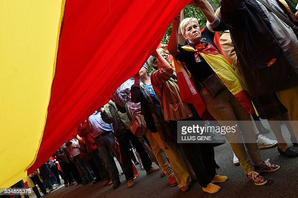 Members of 'La Hermandad de Caballeros Legionarios de Barcelona' hold a giant Spanish flag during a demonstration in support of the Spanish army on...