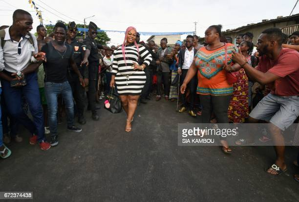 Members of La SAPE movement parade in a street of Abidjan on April 24 2017 during a day of tribute to late Congolese rumba star Papa Wemba as part of...
