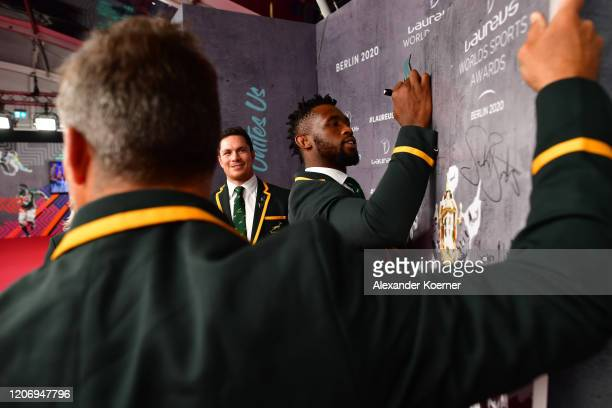 Members of Laureus World Team of the Year the South Africa Mens Rugby Team Schalk Brits Francois Louw and Siya Kolisi sign a wall during the 2020...