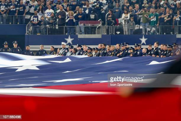 Members of law enforcement hold a field sized United States flag during the national anthem prior to game between the Philadelphia Eagles and Dallas...