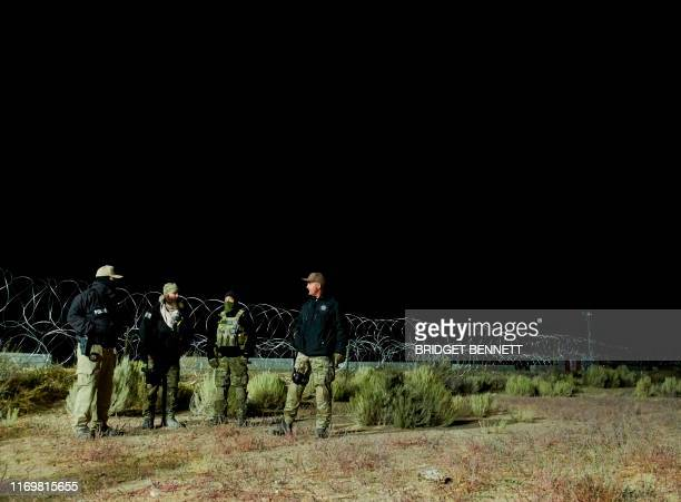Members of law enforcement stand near barb wire as people gathered to storm Area 51 at an entrance to the military facility near Rachel Nevada on...