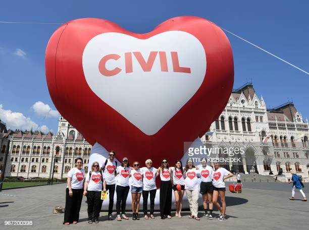 Members of leading Hungarian nongovernmental organisations pose in front of a giant heartshaped balloon during a demonstration calling MP's not to...