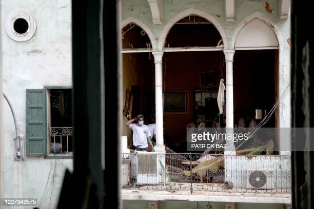 Members of Lebanese civil society clean a damaged apartment in Beirut's neighbourhood of Mar Mikhael on August 7 three days after a massive explosion...