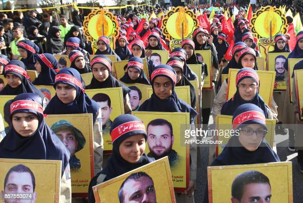 TOPSHOT Members of Lebanon's Shiite Hezbollah scout movement hold portraits of Hezbollah fighters killed while fighting in Syria during a procession...