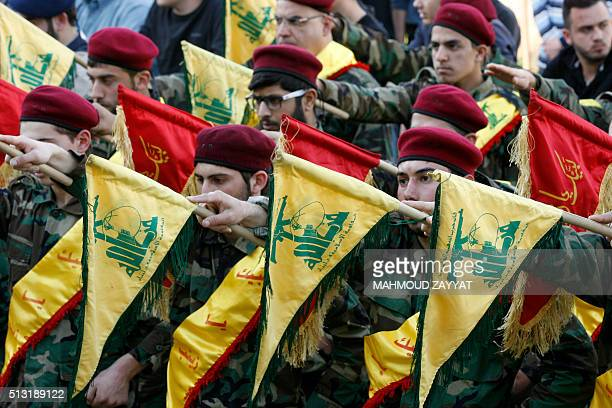 Members of Lebanon's Shiite movement Hezbollah hold their flags on March 1 in the southern town of Kfour in the Nabatiyeh district during the funeral...