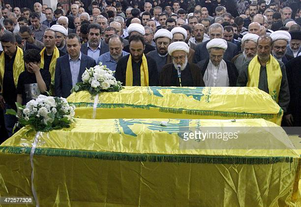 Members of Lebanon's Shiite movement Hezbollah pray in front the coffins of Shiite militants Khodr Aladdine and Hassan Bajouk during their funeral in...