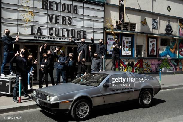 Members of L'European theatre pose with a DeLorean DMC12 car in front of the entrance under the inscription reading Retour vers la culture in Paris...