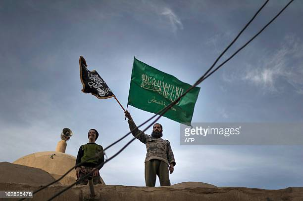 Members of Liwa Hamzah a newly formed Islamist brigade from the Syrian eastern city of Deir Ezzor stand on top of a mosque holding the flags of...