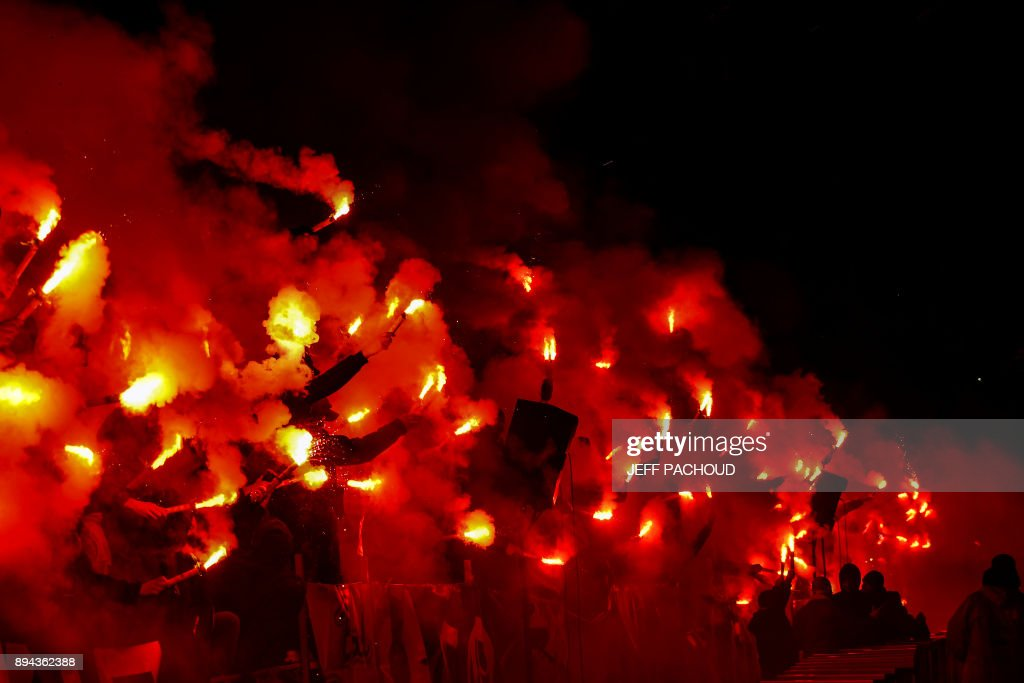 TOPSHOT - Members of Lyons' 'Bad Gones' supporters group hold lit flares to celebrate their 30th anniversary during the French L1 football match Olympique Lyonnais (OL) vs Marseille (OM) at the Parc Olympique Lyonnais stadium in Decines-Charpieu, central-eastern France on December 17, 2017. /