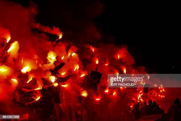 TOPSHOT Members of Lyons' Bad Gones supporters group hold lit flares to celebrate their 30th anniversary during the French L1 football match...