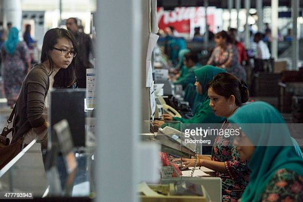 Members of Malaysian Airline System Bhd's ground staff serve passengers at checkin counters at Kuala Lumpur International Airport in Sepang Malaysia...