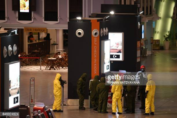 CORRECTION Members of Malaysia's Hazmat team conduct a decontamination operation at the departures terminal of the Kuala Lumpur International Airport...