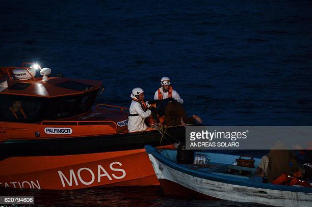 Members of Maltese NGO MOAS and Italian Red Cross help migrants and refugees during a rescue operation of ship Topaz Responder off the Libyan coast...