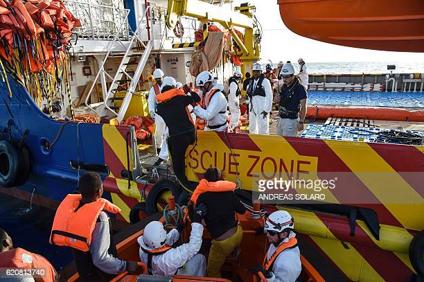 Members of Maltese NGO MOAS and Italian Red Cross help migrants and refugees to board the Topaz Responder ship during a rescue operation off the...