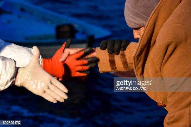 TOPSHOT Members of Maltese NGO MOAS and the Italian Red Cross help an elderly woman to board the Topaz Responder ship during a rescue operation of...