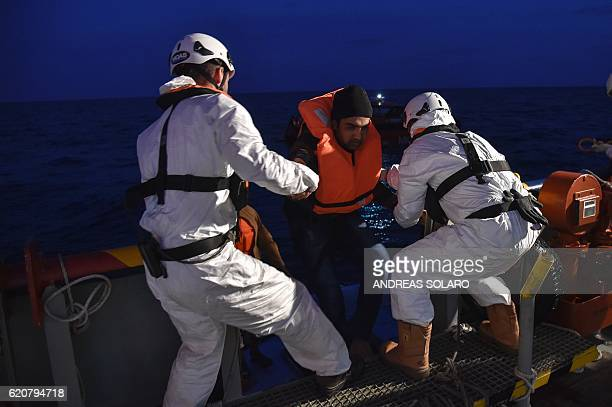 Members of Maltese NGO MOAS and the Italian Red Cross help migrants and refugees to board the Topaz Responder ship during a rescue operation off the...