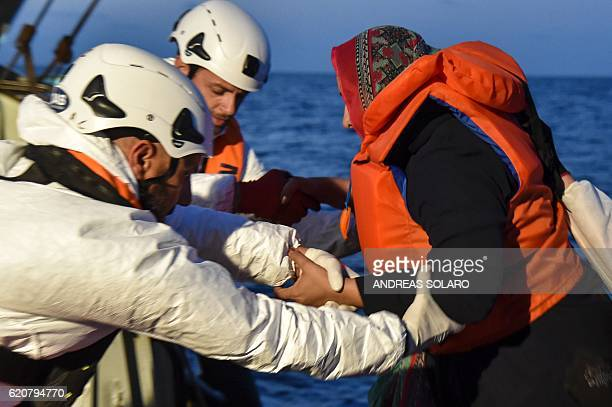 Members of Maltese NGO MOAS help a woman to board the Topaz Responder ship during a rescue operation of migrants and refugees off the Libyan coast in...
