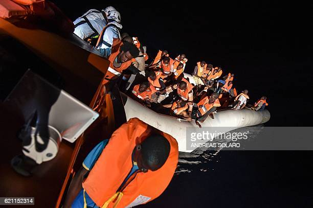 Members of Maltese NGO MOAS helps a man to board a small rescue boat during a rescue operation of migrants and refugees by the Topaz Responder ship...