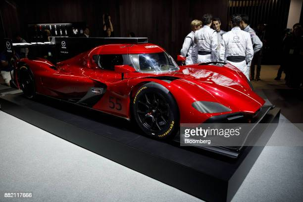 Members of Mazda Team Joest stand next to the Mazda Motor Corp Mazda RT24P racing vehicle after during AutoMobility LA ahead of the Los Angeles Auto...