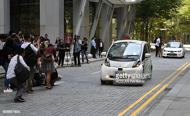 Members of media take picture of Karl Iagnemma chief executive and cofounder of nuTonomy and Grab Singapore head Lim Kell Jay as they ride inside a...