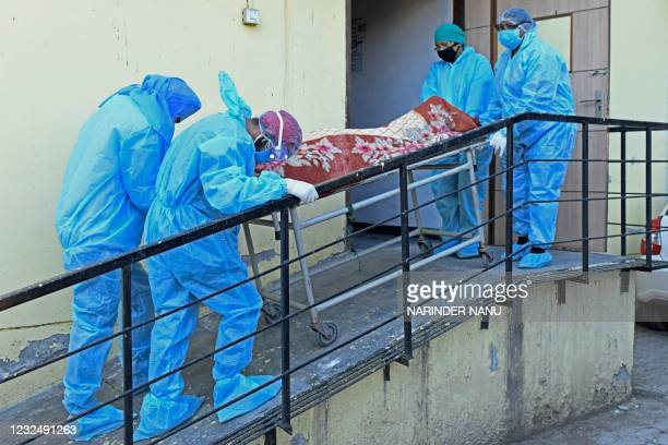 Members of medical staff wearing protective gear carry the dead body of a Covid-19 coronavirus victim at a hospital in Amritsar on April 24, 2021.