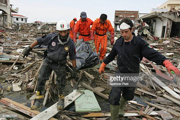 Members of Mexican and German search and rescue teams retrieve a body amongst the rubble of destroyed homes January 14 2005 in Banda Aceh Indonesia...