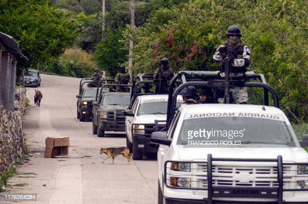 Members of Mexico's National Guard drive by the site where a confrontation between the Mexican Army and armed civilians took place in Tepochica...