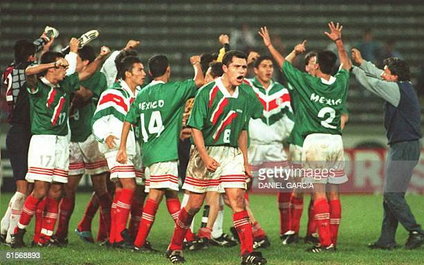 Members of Mexico's Pan American soccer team celebrate on the field following their 21 victory over Colombia 22 March at the 12th Pan American Games...