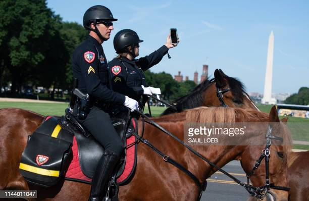 Members of mounted police departments on horseback from around the US walk past the Washington Monument as they arrive to attend the 38th Annual...