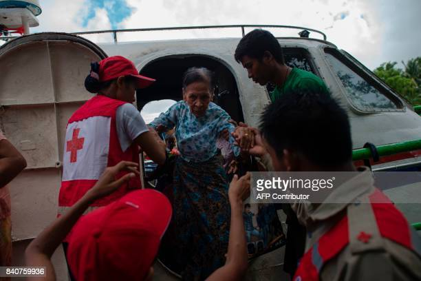 Members of Myanmar's Red Cross help an elderly woman who are fleeing a conflict area as she arrives in Sittwe jetty in Rakhine State on August 30...