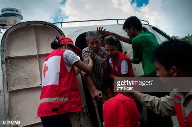 TOPSHOT Members of Myanmar's Red Cross help elder woman who is fleeing a conflict area upon arriving in Sittwe jetty in Rakhine State on August 30...