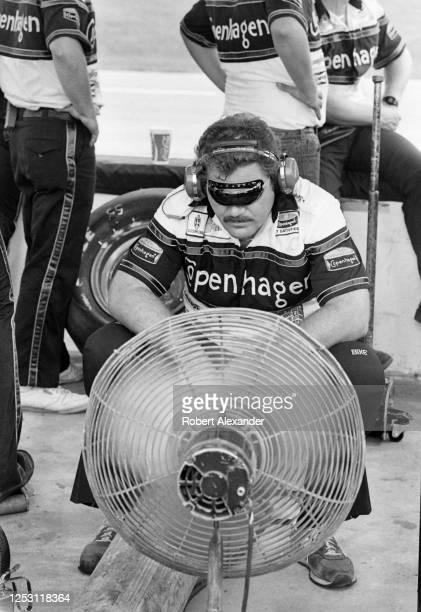 A members of NASCAR driver Benny Parsons' crew cools off in front of a fan during the running of the 1985 Pepsi Firecracker 400 stock car race at...