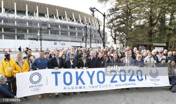 Members of national Olympic committees pose for photos on March 18 in front of Japan's new National Stadium the main venue for the 2020 Tokyo...