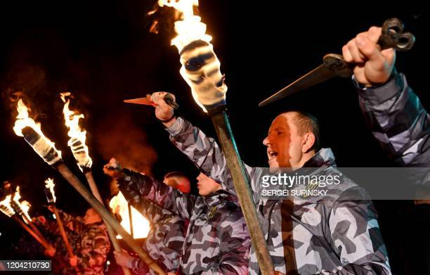 Members of National Voluntary Squads, Ukrainian far-right organization, hold torches and ritual dirks in Kiev on February 29, 2020 during the...