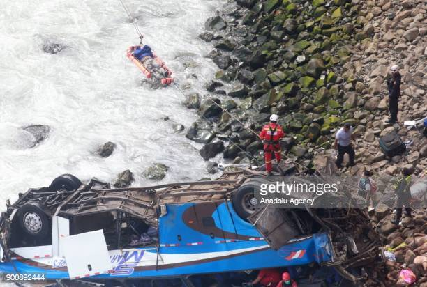 Members of NGO carry a dead body on a stretcher after a bus plunges off the cliff following a collision with a tractor in Lima Peru on January 03...