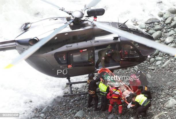 Members of NGO carry a dead body on a stretcher to a helicopter after a bus plunges off the cliff following a collision with a tractor in Lima Peru...