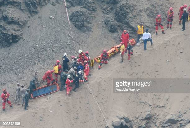 Members of NGO carry dead bodies on a stretcher after a bus plunges off the cliff following a collision with a tractor in Lima Peru on January 03...