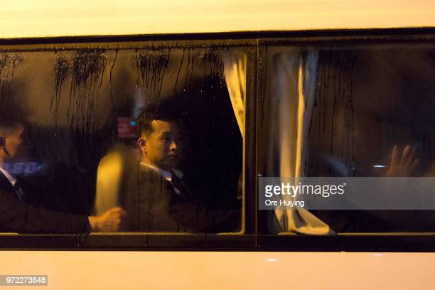 Members of North Korean leader Kim Jongun's convoy look out the window of a bus as the motorcade departs for the airport on June 12 2018 in Singapore...