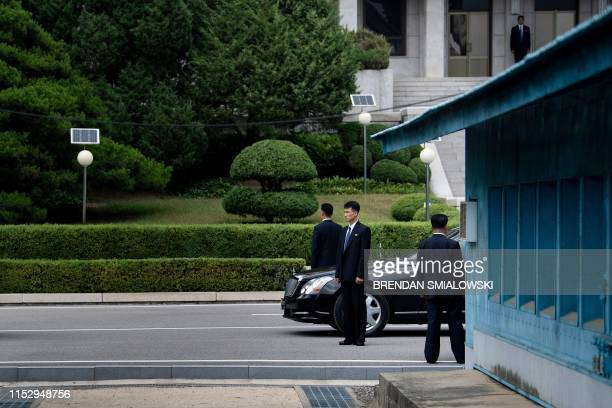 Members of North Korean security stands guard near a North Korean motorcade while US President Donald Trump and North Korea's leader Kim Jong-un meet...