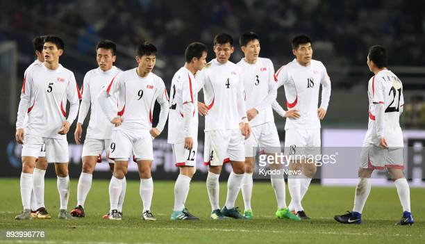 Members of North Korea's national football team gather on the field after tying China 11 in the E1 Football Championship at Ajinomoto Stadium in...