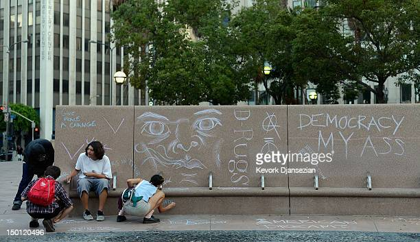 Members of Occupy Los Angeles write chalk messages at Pershing Square near the ArtWalk which takes place along Spring Street between Third and...