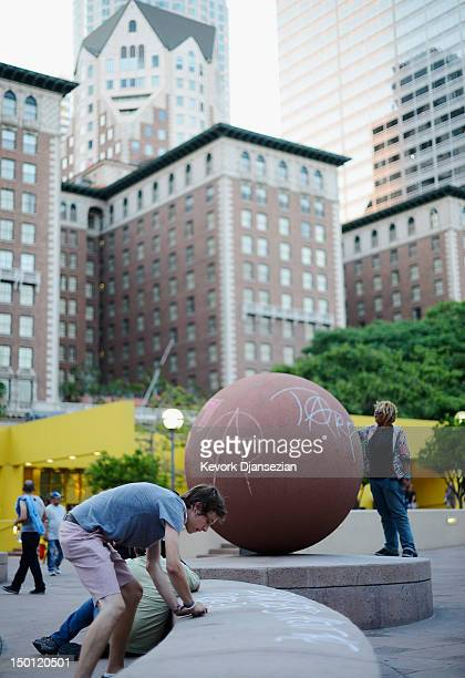 Members of Occupy Los Angeles write chalk messages on a sculpture at Pershing Square near the ArtWalk which takes place along Spring Street between...