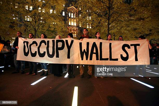 Members of Occupy Wall Street stand in triumph after a court order allowed them to reenter Zuccotti Park late Tuesday afternoon.