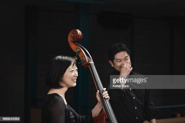 Members of orchestra talking and smiling at concert hall