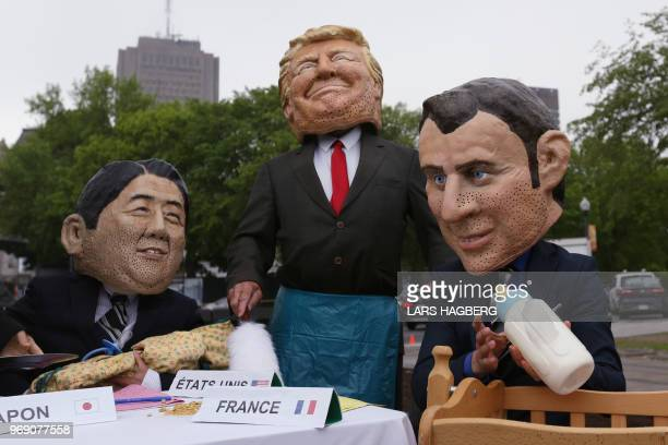 TOPSHOT Members of OXFAM dressed as Japanese Prime Minister Shinzo Abe US President Donald Trump and French President Emmanuel Macron pose for...