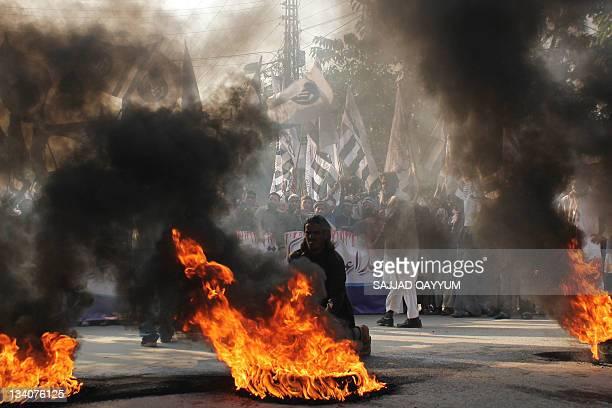 Members of Pakistan's banned Islamist groups including JamaatudDawa JaisheMohammad and LashkareTaiba gather beside burning tires during an antiIndian...