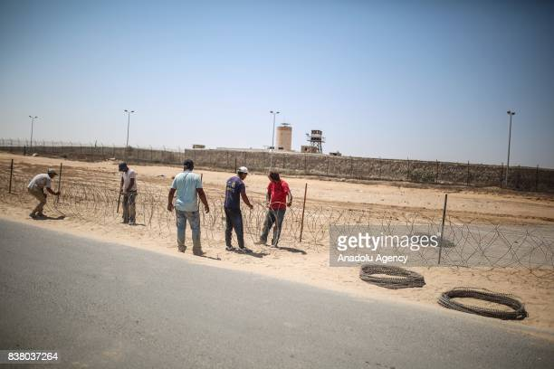Members of Palestinian Legislative Council's committee set up wires at the border in Gaza City Gaza on August 23 2017 A committee of Palestinian...