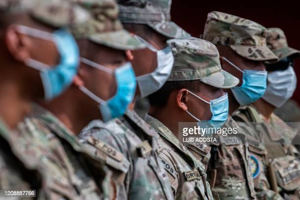 Members of Panama's National Border service wear face masks as they assist volunteers of Panama Solidarity Plan arranging food before the delivery of...