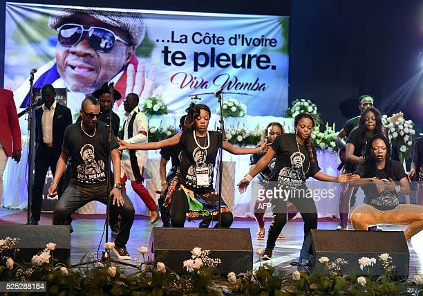 Members of Papa Wemba's music group dance and sing during a concert in tribute to him on April 27 2016 at the Palace of Culture in Abidjan The...